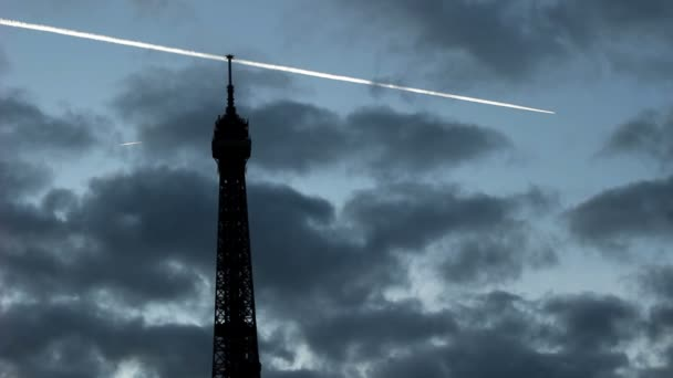 Plane flies in the clouds above the Eiffel Tower