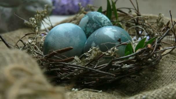 Schwenkkkamerafahrt auf Osternest mit eingefärbten blauen Eiern