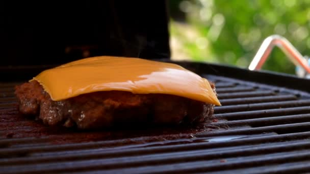 Piece of cheese is melted on a hot beef burger