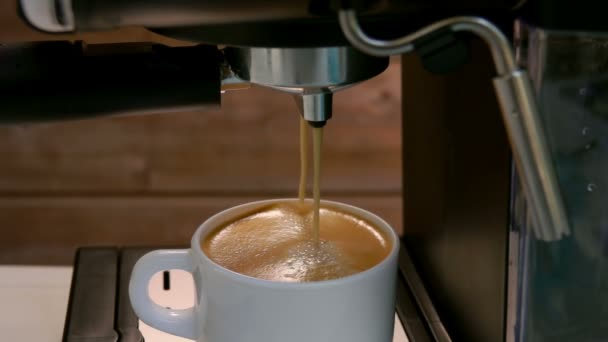 Espresso coffee is poured into a white cup