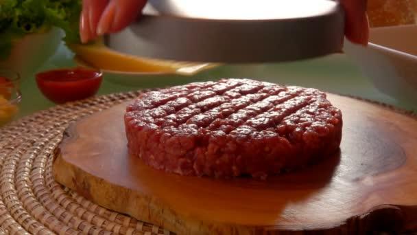 Kotlet na hamburger leží na dřevěné desce