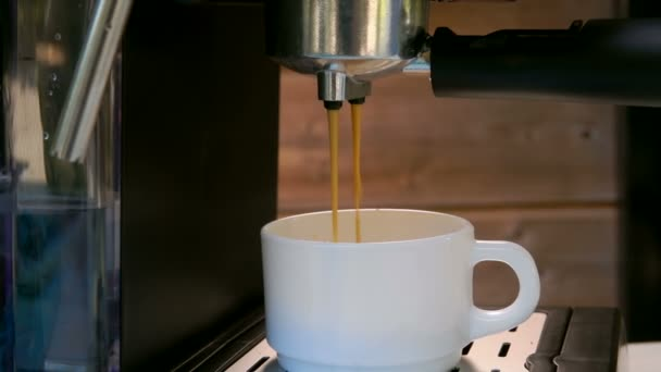 Espresso-Kaffee wird in eine weiße Tasse gegossen