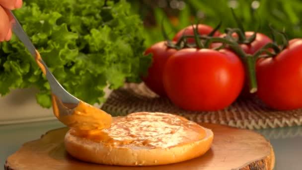 Spoon smears the sauce onto a hamburger bun
