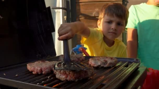 Chlapec stiskne kotlet na grilu stěrkou