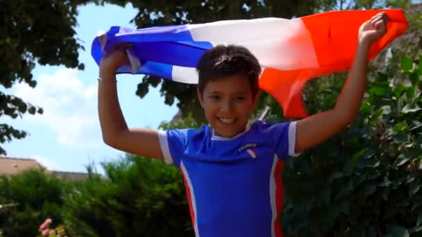 Boy jumping for joy with a French flag in his hands