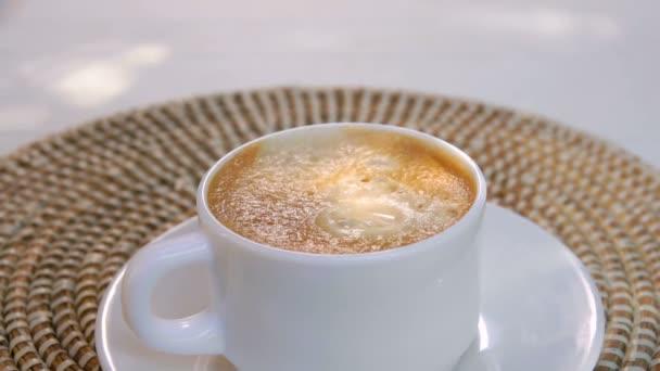 Piece of sugar falls into a cup of espresso coffee