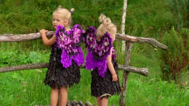 Gyönyörű lányok lila pillangó szárnyakkal állnak a hídon a szabadban.