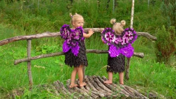 Aranyos szőke lányok lila pillangó szárnyakkal állnak a fa hídon.