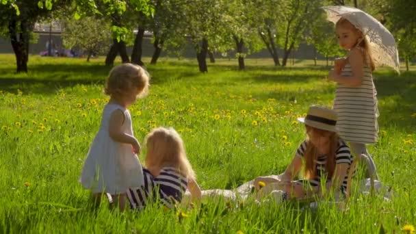 Vier Mädchen in gestreiften Kleidern sitzen im Garten und lesen ein Buch