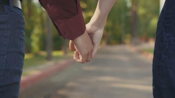 Young couple walking together holding hands from close up rear view perspective