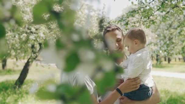 Smiling caucasian parents holding up cute son in summer apple tree park