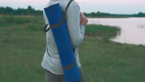 Mladá dívka procházka praxe jógy na pobřeží. Žena hospodářství blue jóga mat