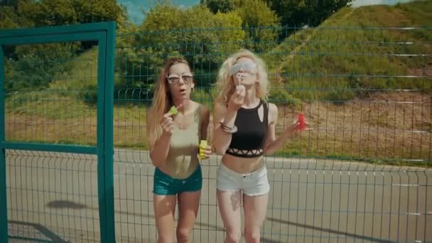 Beautiful hipster girls in sunglasses having fun making bubbles outdoors