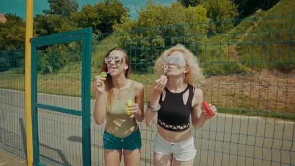 Dívky v sluneční brýle baví dělat bubliny venku