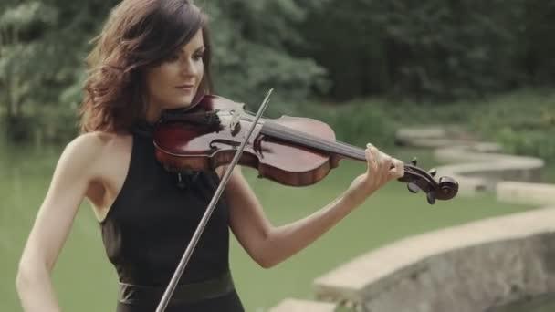 Ruha szép lány játszik hegedű szabadban. Elegáns hegedűművész-erdő