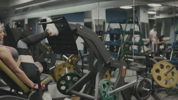 starkes Mädchen beim Sport auf Sportgeräten für Beine im Fitnessstudio