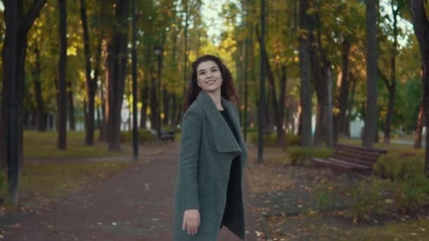 Amazing girl in romantic look, with curly hairstyle in coat walk in autumn alley