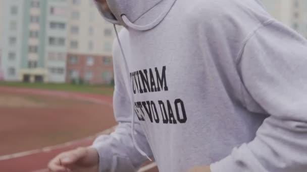 Mladý muž běží v hoodie venku. Boxer trénink na stadionu v ranní