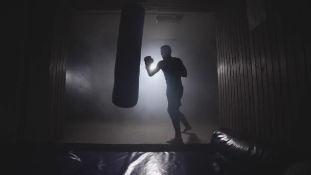 Boxovací pytel silný atlet v tmavých tělocvičně ve zpomaleném filmu. Mladý muž, školení