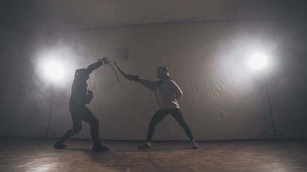 Warriors are fighting during sword battle indoors in slow motion