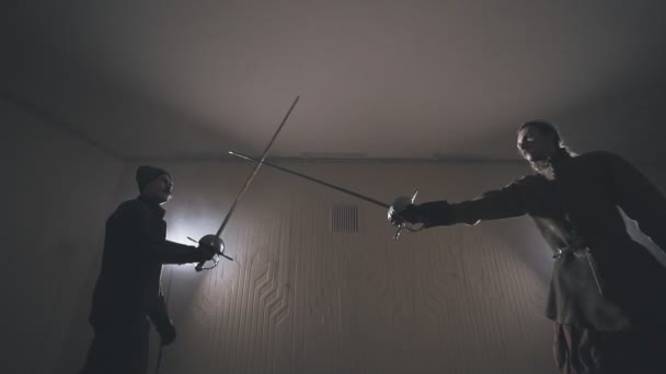 Medieval warriors training with swords indoors in slow motion