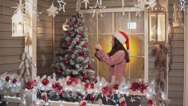 Young woman decorates Christmas tree by red balls, girl decorates Christmas tree