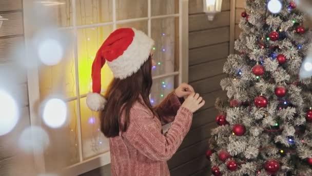 Hezká dívka v svetr a santa čepici zdobí vánoční strom do červené koule