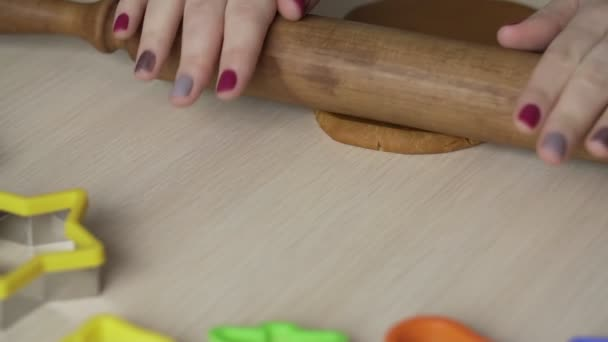 Female hands roll dough with rolling pin for christmas cookies on white table