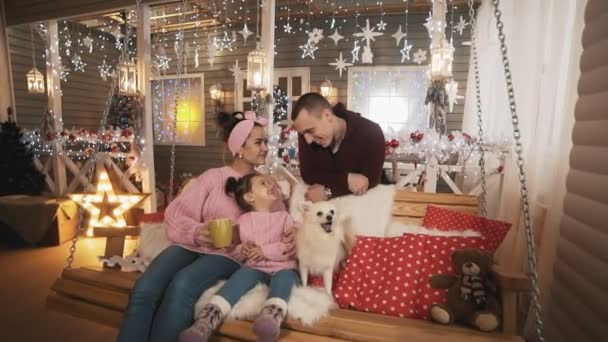 Family with daughter and white dog have fun sitting at Christmas bench at porch
