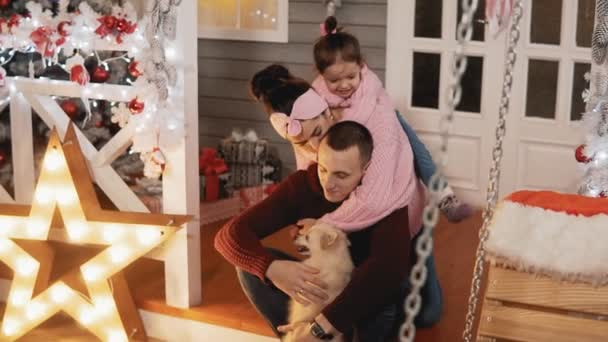Happy family of mother, father, daughter and dog have fun at Christmas porch