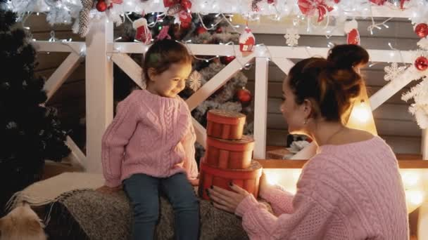 Mother presenting surprise gift box to little daughter in slow motion