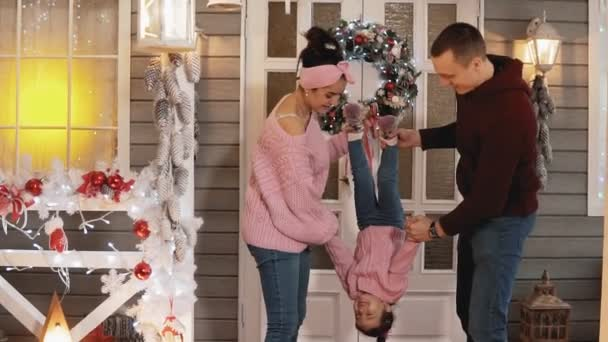 Joyful family with daughter have fun at Christmas porch.