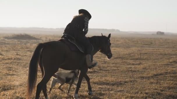 Krásná žena na koni při východu slunce v oboru. Mladí cowgirl na hnědý kůň