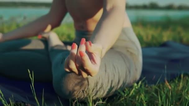 Rukou ženy v lotosové pozici při západu slunce. Holka dělá jógu v večer u jezera