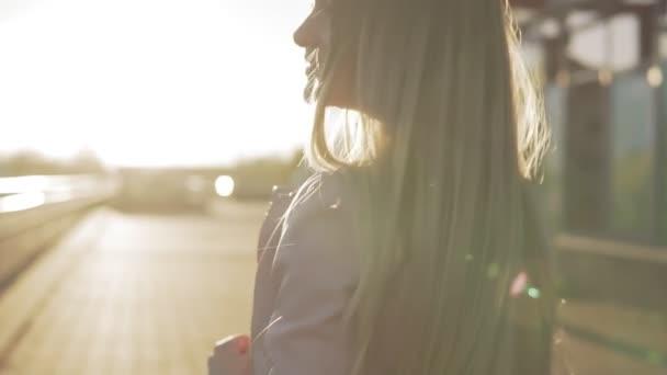 Krásná blondýnka se usmívá na kameru a hledě při západu slunce
