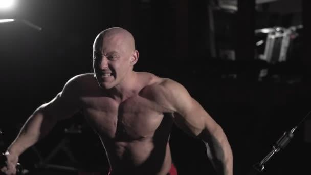 Mužského kulturista trénink hrudníku svaly vykonávají kabelem kříž nad strojem pro tělesné hmotnosti. Muž v tmavých tělocvičně dělá táhne hmotnost cvičení v pomalém pohybu. Sport koncept cvičení a kulturistika