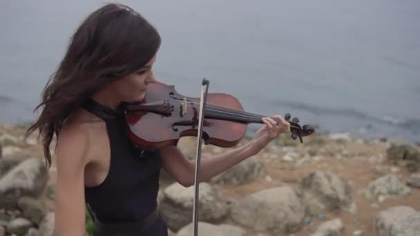 Gyönyörű lány hegedű. A ruha a fiatal hegedűművész játszik a háttérben tenger
