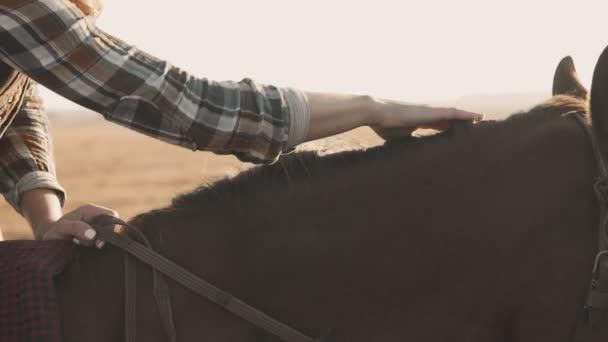Nahaufnahme einer jungen Frau, die auf einem Pferd sitzt und Pferdemähne mit der Hand streichelt