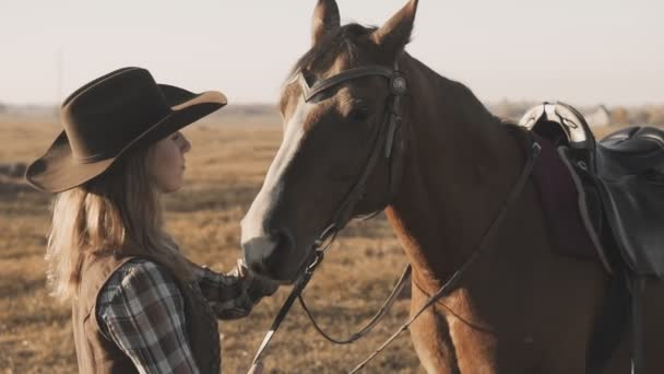 Mladá blondýnka s dlouhými vlasy v kovbojském klobouku hladit a objímat koně