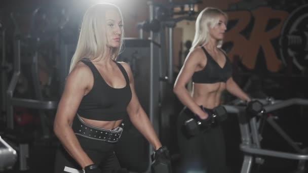 Workout of two blonde girls in dark gym. Motivation healthy lifestyle