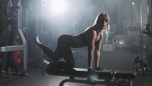 Sexy blonde Frau im dunklen Sportzentrum in Zeitlupe training