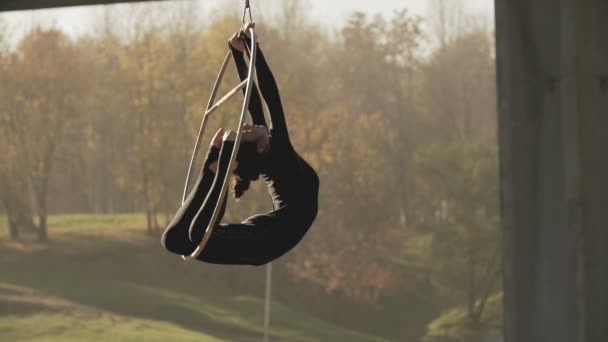 Flexible brunette doing some acrobatic elements on aerial hoop outdoors