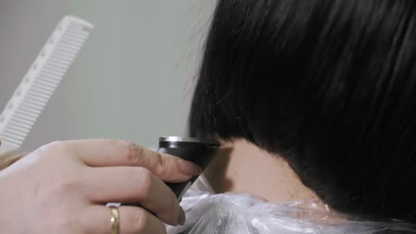 Hairdresser trimming brown hair with electric razor in slow motion