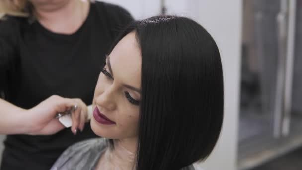 Ženské kadeřnice vlasy hřebenem. Zblízka. Salon krásy