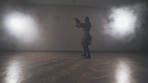 Medieval warrior training with two-handed sword indoors in slow motion