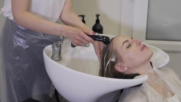Mytí blond žena v salonu krásy. Krásná holka myje vlasy v salonu