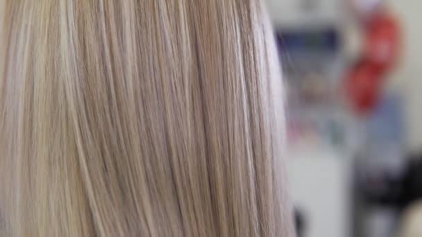 Zblízka pohled blond vlasy. Krásná mladá dívka v salonu krásy.