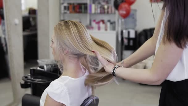 Young beautiful girl in beauty salon. Hairdresser stylist makes girls hair