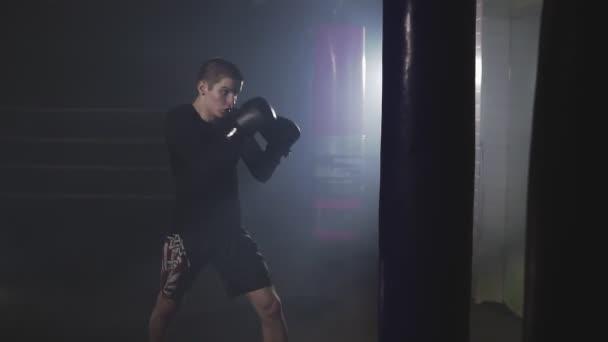 Muay thai Kämpfer Stanzen in rauchigen Studio. Kickboxer training mit Boxsack