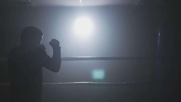 Ausbildung in niedrigen Leuchtring Kickboxer. Silhouette auf dunklem Hintergrund